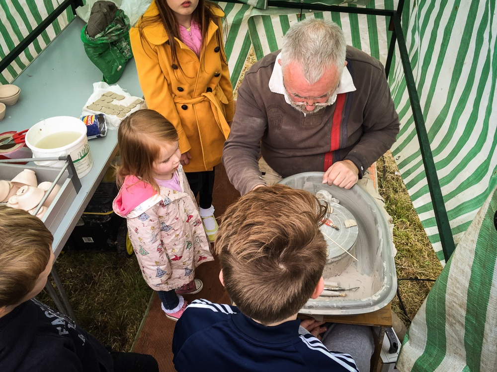 Potter Bill entertains young visitors with his wearable sculptures